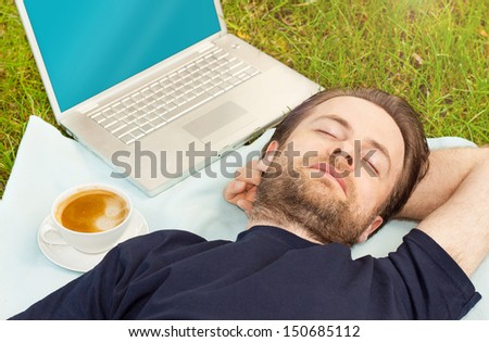 Man sleeping outdoor on grass next to a coffee and laptop computer - freelance work or exhausted designer concept - stock photo