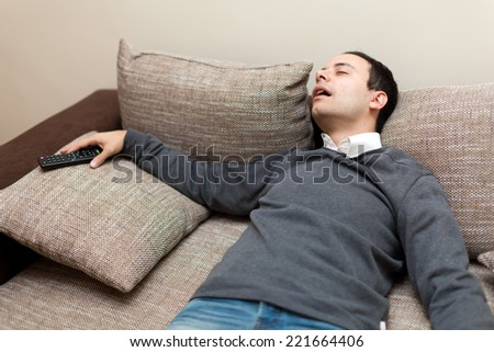 Man sleeping while watching tv - stock photo