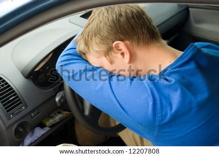 man sleeps in a car - stock photo