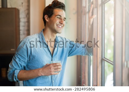 Man Smile Drink Cup of Coffee Looking to Window - stock photo