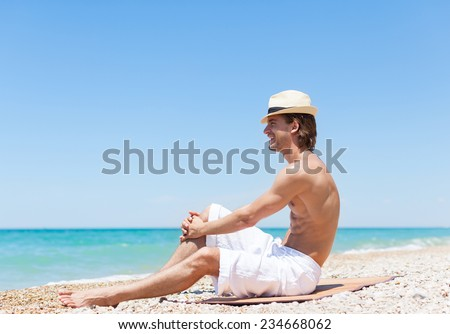 man smile sitting on beach summer vacation looking far away to horizon copy space, Handsome young male wear hat, sun tanned body, guy over sea blue sky, concept ocean holiday travel
