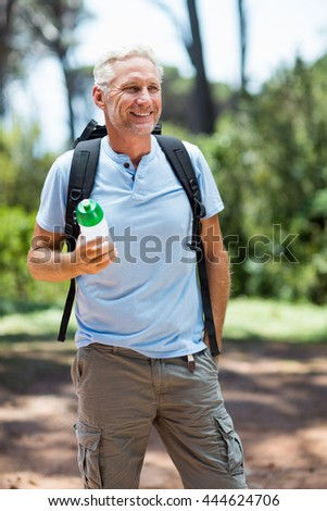 Man smiling and holding a flask on the wood