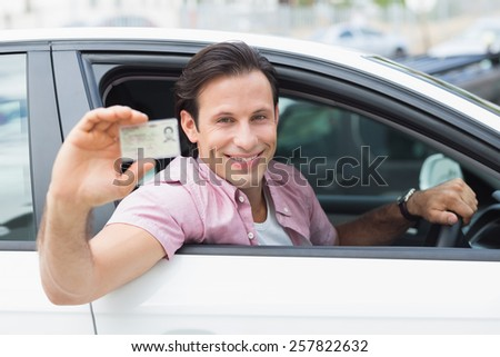 Man smiling and holding his driving license in his car - stock photo