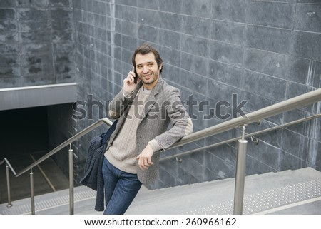 man smiling and talking with smartphone - stock photo