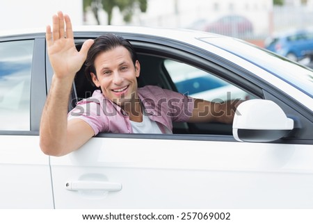 Man smiling and waving in his car - stock photo