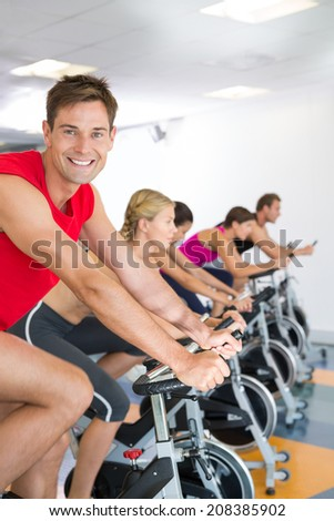 Man smiling at camera during spin class at the gym