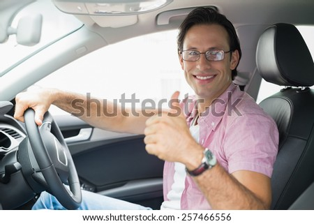 Man smiling while driving in his car - stock photo
