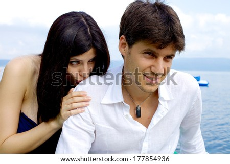 Man smiling while girlfriend asks to forgive her - stock photo