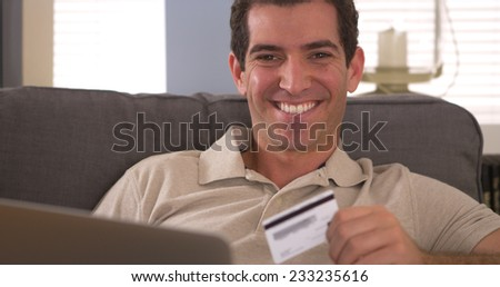 Man smiling with credit card and laptop - stock photo