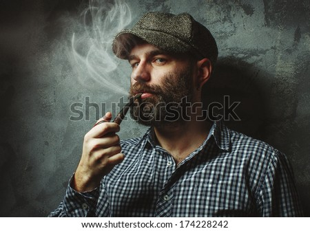 Man smoking a pipe standing near the wall textured