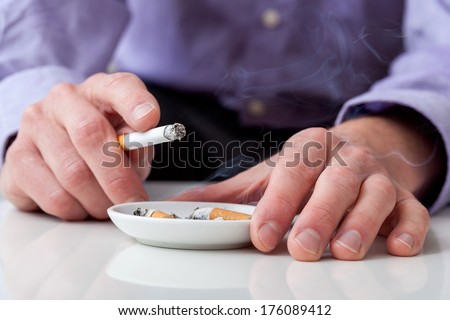 Man smoking cigarette and using an ashtray - stock photo