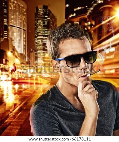 Man smoking cigarette outdoors - stock photo