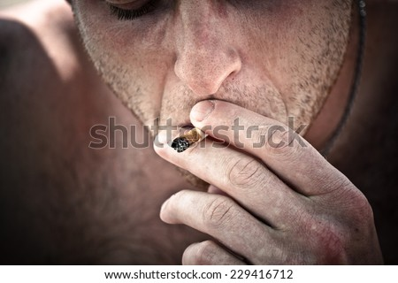 Man smoking hashish joint. - stock photo