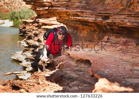 Man sneak along rock edge at Loop walk, Kalbarri national park, Western Australia - stock photo