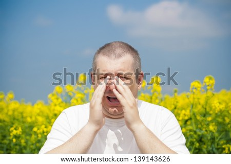 Man sneezes on canola field - stock photo