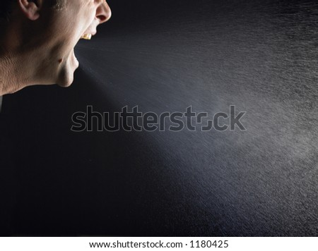 Man sneezing over black background