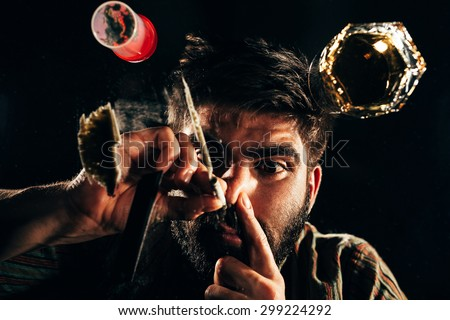 Man sniffing cocaine or other illegal drugs in line using dollar bill  - stock photo