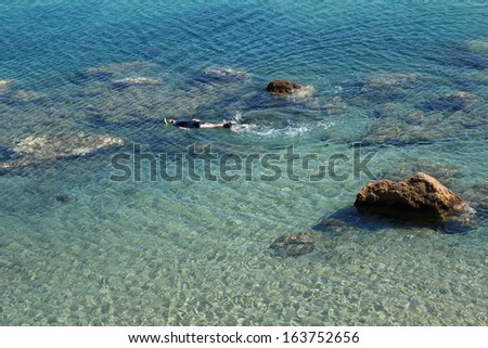 man snorkeling in crystal clear water - stock photo