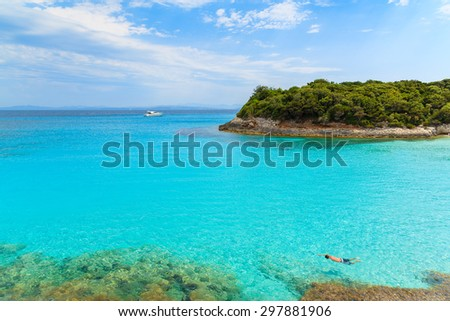 Man snorkeling in turquoise sea water of Petit Sperone bay, Corsica island, France - stock photo