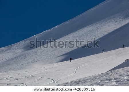 Man snowboarder snowboarding on fresh white snow on ski slope on Sunny winter day  - stock photo