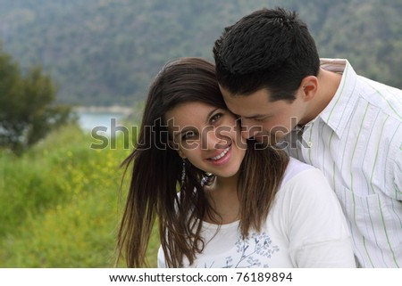 Man Snuggling and Kissing Attractive Woman - stock photo