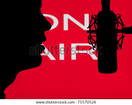 man speaking into the microphone with on the air sign in the background,for entertainment,broadcasting,sound themes - stock photo