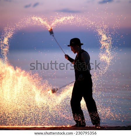 Man spinning poi making heart of fire sparks, declaration of love  - stock photo