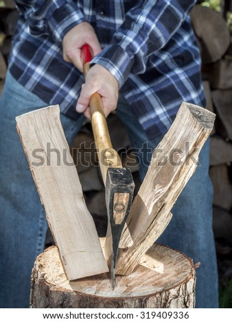 Man splitting log on chopping block with axe