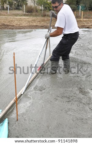 Man spreading concrete foundation - stock photo