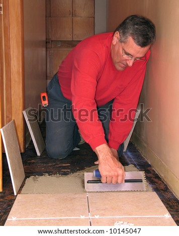 Man spreading mortar to install ceramic tiles - stock photo