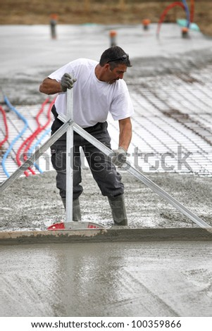 Man spreading wet cement - stock photo