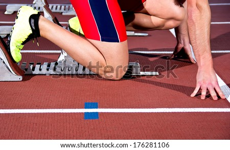 Man sprinter leaps from starting block.