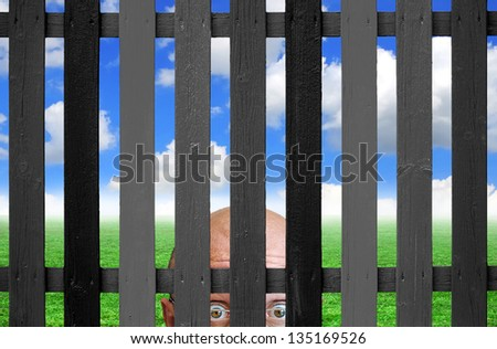 Man spying behind a fence - stock photo