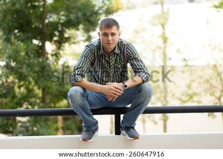 Man squatting on a railing - stock photo