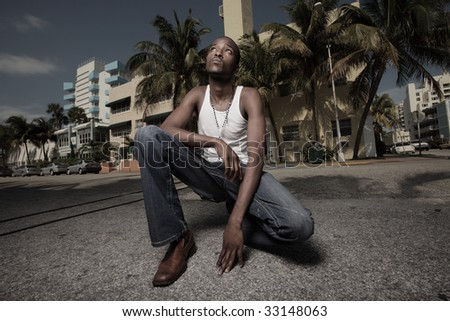 MAn squatting on the street and glancing away - stock photo