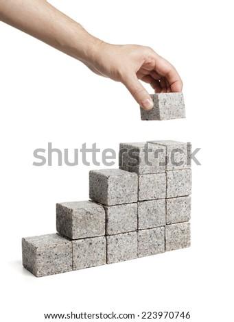 Man stacking blocks made of granite rock. - stock photo