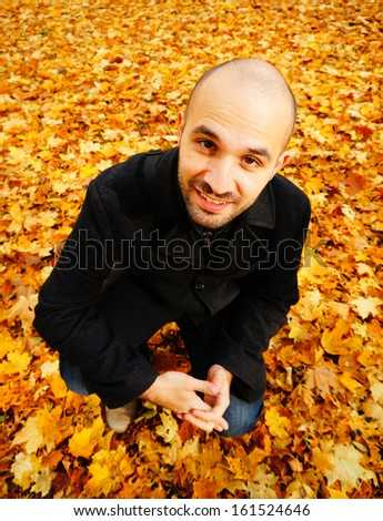 Man stading on many leaves in the autumn season