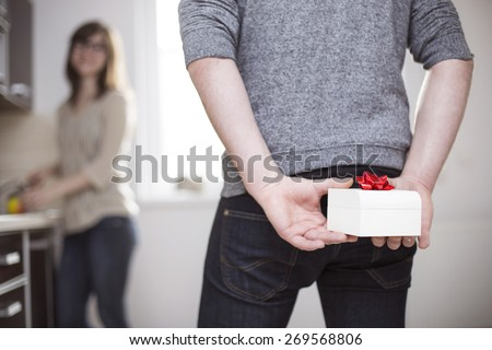 Man standing and holding white gift box behind his back - stock photo