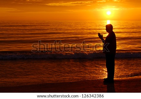 Man standing and praying at the ocean with orange sunset in background - stock photo