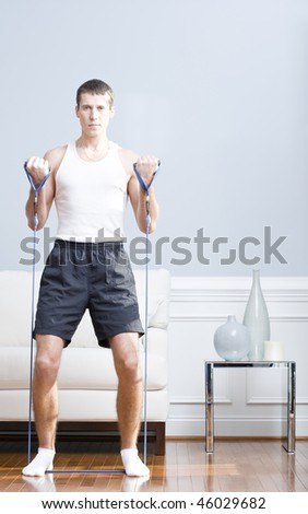 Man standing and using resistance bands in his living room. Vertical format. - stock photo