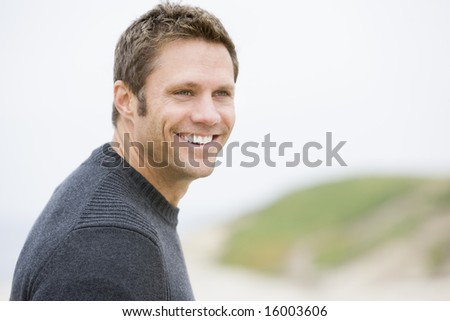 Man standing at beach smiling - stock photo