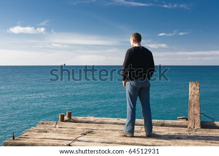 Man standing at pier and looking at the sea