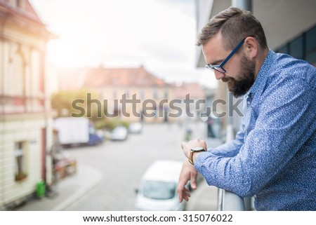 Man standing at terrace and looking at hand watch - stock photo