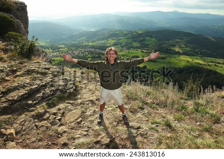 man standing at the top of a mountain, achievement concept - stock photo