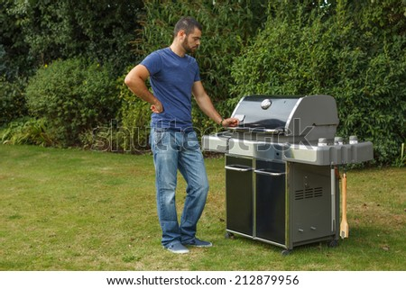 Man standing by a grill in his backyard