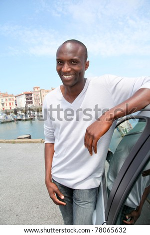 Man standing by car in tourist town - stock photo