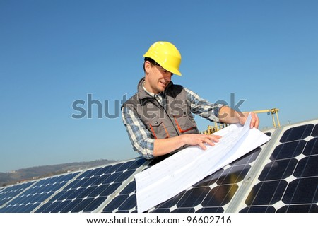 Man standing by solar panels with construction plan - stock photo