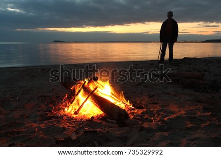 Man standing by the bonfire near the river at sunset, Ob River, Siberia, Russia