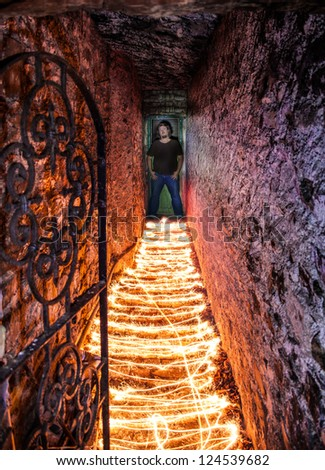 Man standing in a tunnel and the floor covered with burning material