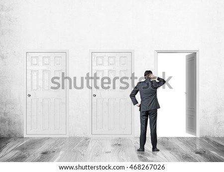 Man standing in concrete wall corridor with three doors. One open, two closed. Concept of finding right way to solve problem.